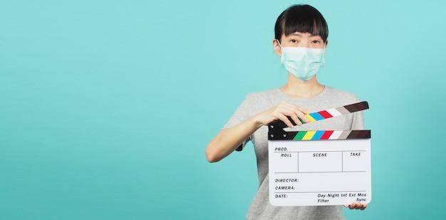 女の子または女性は、白い背景の上のビデオ制作、映画、映画産業で使用するフェイスマスクと手持ちの黒いカチンコまたは映画スレートを着用します。