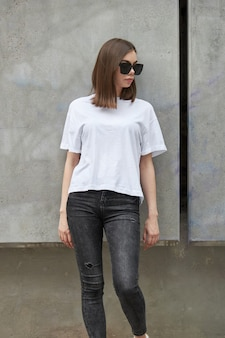 Девушка или женщина в белой пустой футболке с местом для вашего логотипа, макета или дизайна в повседневном городском стиле