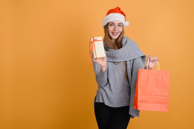 Girl on an orange background holds a package and a gift in her hand.