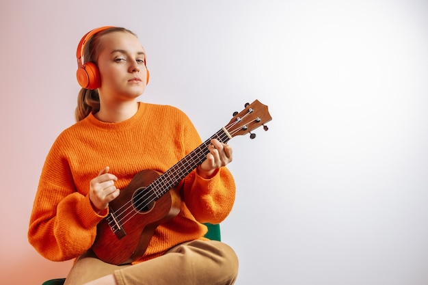 A girl in an orange sweater and headphones plays a ukulele on a light background