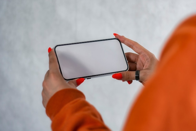 Girl in an orange sweater with beautiful nails holds a smartphone mockup with white screen in hands. mock-up technology.