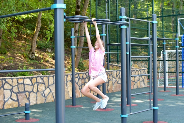 Girl on outdoor sports field. teenager girl doing gymnastic exercises at outdoor gym.