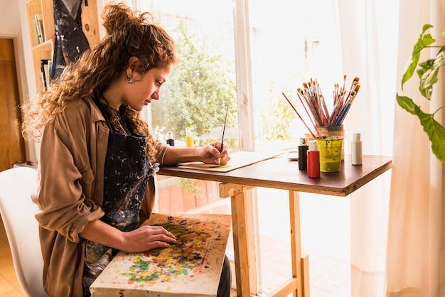 Девушка рисует холст