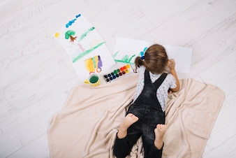 Girl painting by water colors on paper and lying on floor