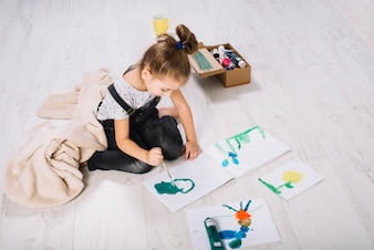 Girl painting by water colors on paper near container and sitting on floor
