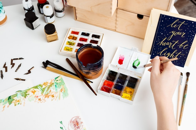 水彩で紙に絵を描く少女。