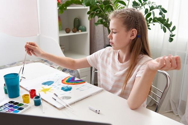 Girl painting at home, rainbow art drawing