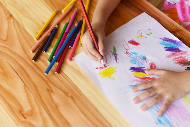 自宅の木製のテーブルに色鉛筆で紙に絵の女の子-絵とカラフルなクレヨンを描く子子供