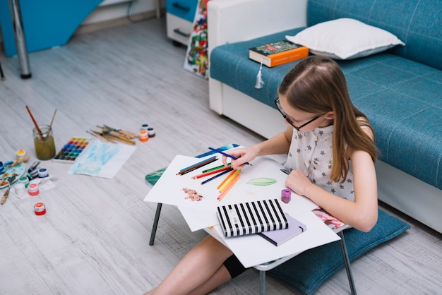 Girl painting on paper at table with set of pencils in room with water colors on floor