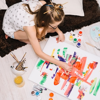 Girl painting with bright gouache on paper on floor