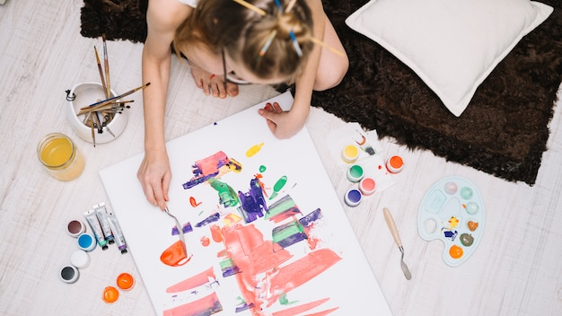 Girl painting with gouache on paper on floor