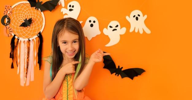オレンジ色のハロウィーンの背景に分離されたコピースペースで脇に2本の指で絵を描く女の子