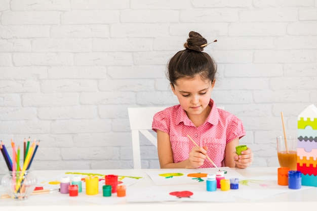 A girl painting with watercolors on table against white brick wall