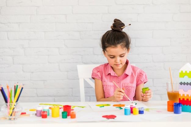 Una ragazza che dipinge con gli acquerelli sulla tavola contro il muro di mattoni bianco