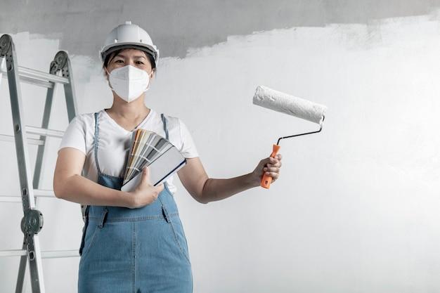 소녀는 롤러로 흰 벽을 그립니다. 인테리어 수리. 빈 방에 벽을 그리는 젊은 여성 장식가, 컨셉 빌더 또는 빈 방 위에 페인트 롤러가 달린 헬멧을 쓴 화가.