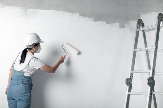 소녀는 롤러로 흰 벽을 그립니다. 인테리어 수리.