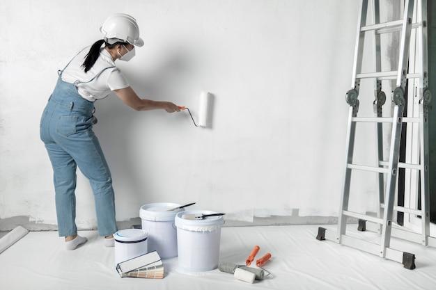 소녀는 롤러로 흰 벽을 페인트