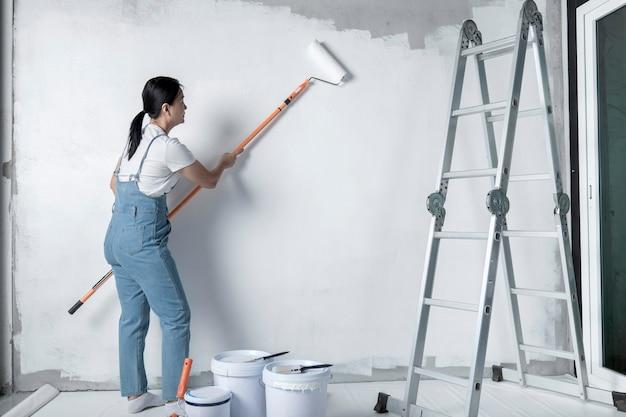소녀는 롤러로 흰 벽을 그립니다.