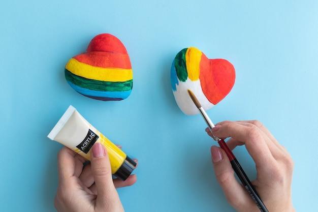 Девушка рисует сердце в цвета радуги, концепция свободной любви лгбт.