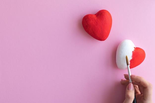 Девушка рисует сердца в красном, розовом фоне, место для текста.