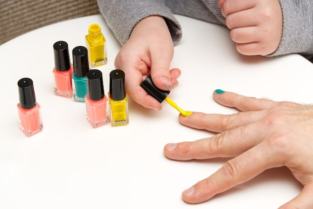 Girl paints her dad's nails with various colors. lgbt family concept