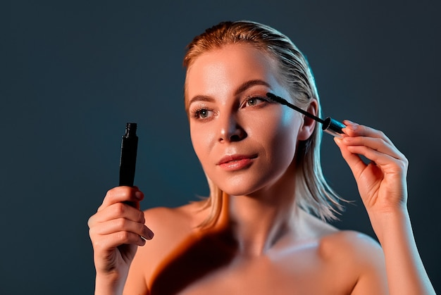 The girl paints her eyelashes with mascara.