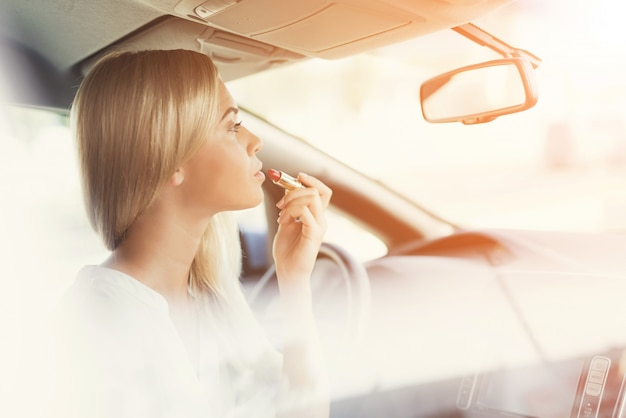 Girl paints her lips while sitting at wheel.
