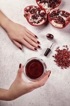 女の子は爪にジェルポリッシュを塗ります。白い背景、グラスワイン、赤のディテール。美しい手。ネイルエクステンション。マニキュア、スパサロン。クリエイティブ、広告。リラックス。