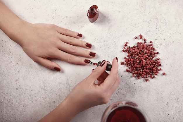 女の子は爪にジェルポリッシュを塗ります。白い背景、グラスワイン、赤のディテール。美しい手。ネイルエクステンション。マニキュア、スパサロン。クリエイティブ、広告。
