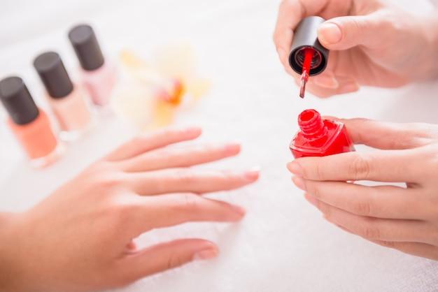 여자는 살롱에서 붉은 광택으로 손톱을 그립니다.