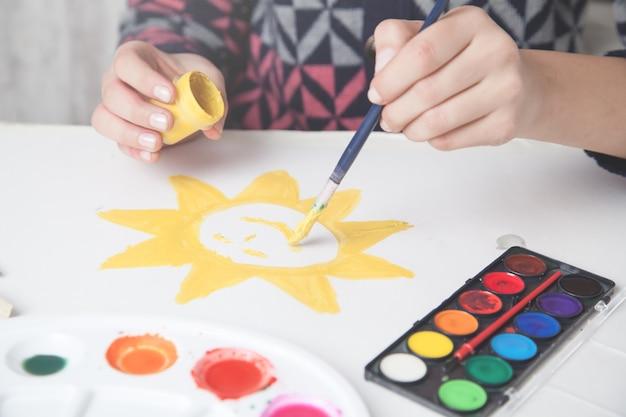 Девушка рисует солнце на бумаге кистью.