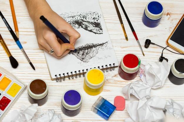 소녀는 그래픽 기술로 풍경을 그립니다. 소녀 예술가의 손과 앨범 페이지, 페인트, 연필, 기름, 나무 배경에 브러시
