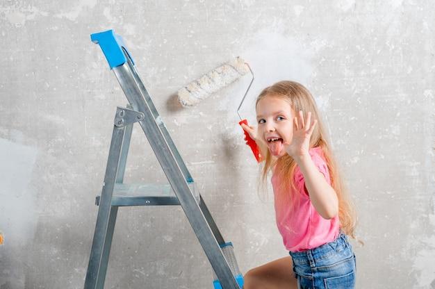 女の子は部屋のローラーで壁をペイントします家族のリフォーム家家の修理とリフォーム