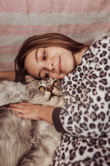 Girl in pajamas and cat in the bed