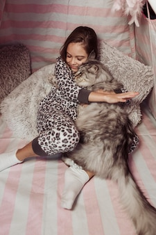 Girl in pajamas and cat hugging