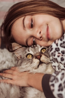 Girl in pajamas and her cute cat