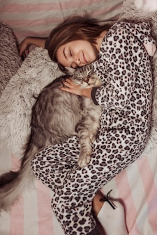 Girl in pajamas hugging her cat and laying on the bed