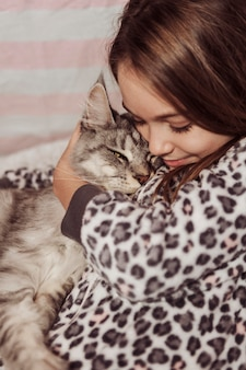 Girl in pajamas hugging her cat