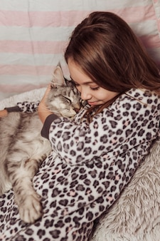 Girl in pajamas hugging her fluffy cat