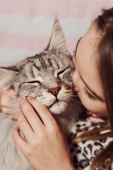 Girl in pajamas kissing her cat