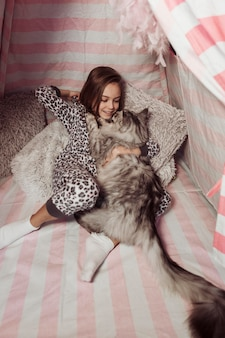 Girl in pajamas and at with long tail