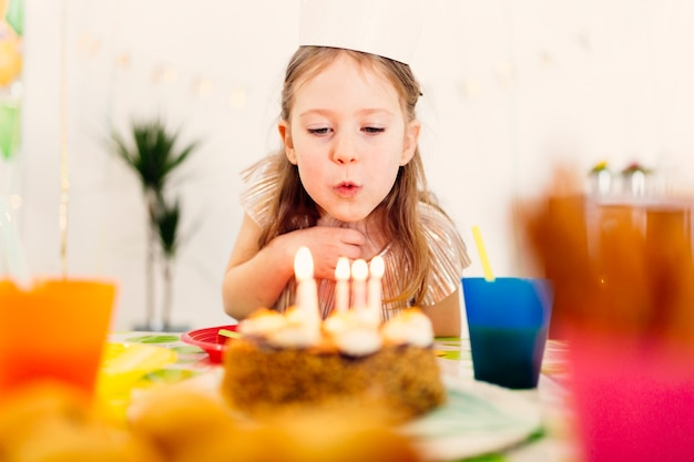 Girl in paper crown blowing candles