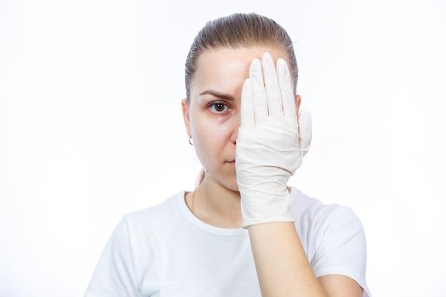 女の子の救急隊員は手に白い医療用手袋を着用します。細菌やウイルスに対する保護。彼女は白い背景に白いtシャツを着ています。
