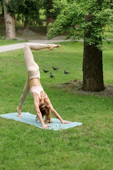 Girl in the park does yoga in the morning in summer