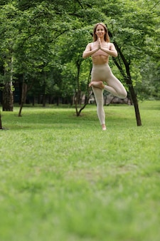 Girl in the park in the position of the tree is engaged in yoga in the summer