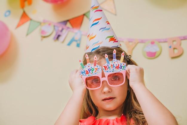Girl in party glasses celebrating birthday