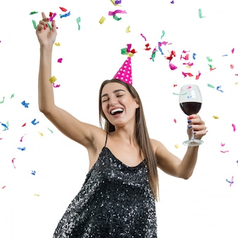 Girl in party hat with glass of red wine dancing under confetti