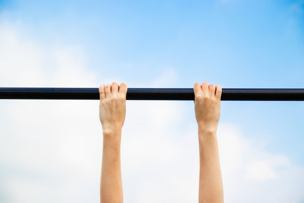 Girl passes the standards for pulling up on a horizontal bar in the park sunny day.