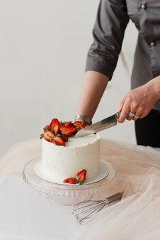 소녀 생과자 요리사는 칼로 크림과 함께 흰색 딸기 케이크를 자른다.