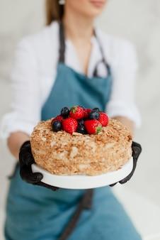 ベリーの甘い食べ物と蜂蜜ケーキを保持している女の子のパティシエ